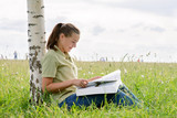 student girl reading a big book sitting on grass