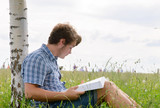 Student boy reading a big book sitting on grass