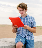 Student boy reading on stone promanade