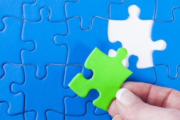 Woman's hand placing missing piece in Jigsaw puzzle  signifying