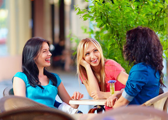 happy friends talking in summer cafe, urban outdoors