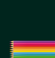 Colored pencils in front of a blackboard.