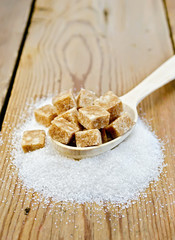 Sugar brown and granulated sugar in a spoon on the board