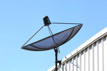Satellite TV receiver on blue sky background.