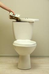 Hand hides money in toilet tank in a bathroom