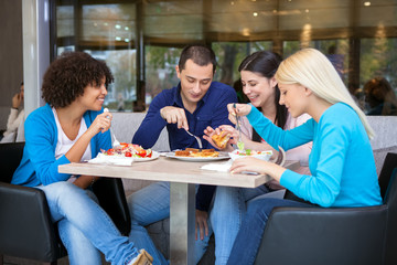 Cheerful teenagers having lunch in restaurant
