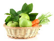 Juicy green apples and carrots with leaves in basket, isolated