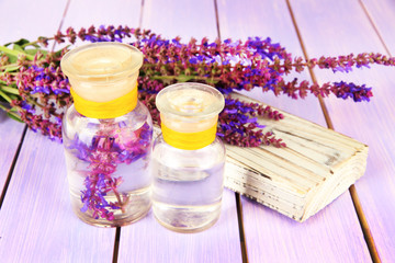 Medicine bottles with salvia flowers on purple wooden