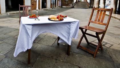 Tavolo apparecchiato con sedie in piazza