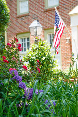 American Flag on Brick Home Behind Garden
