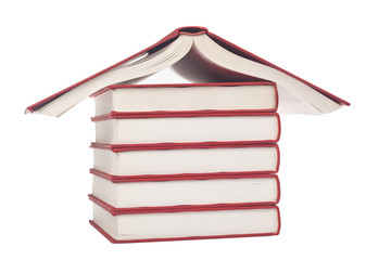 Stack of books forming the shape of a house isolated on white