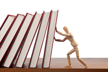 Figurine stopping a domino effect caused by falling books