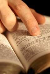 Close-up of Bible opened on Psalm 23 and pointing finger