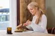 Young Woman Eating Burger At Restaurant