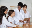 Teacher Showing Digital Tablet To Female Students In Science Lab