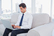 Businessman using laptop on a couch