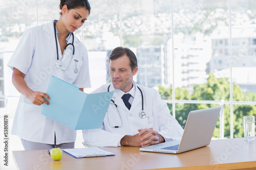 Doctor showing a folder to a colleague