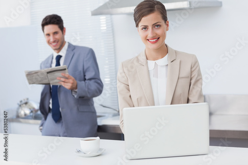 Businesswoman using a laptop while having breakfast