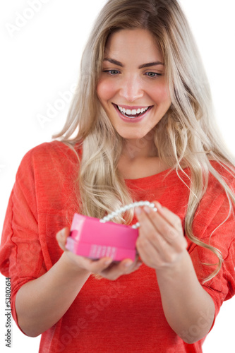 Blonde woman discovering necklace in a gift box