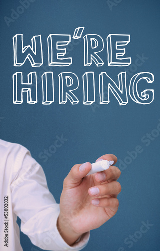 Hand holding a marker and writing we're hiring
