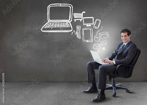 Businessman typing on his laptop with media device graphics comi
