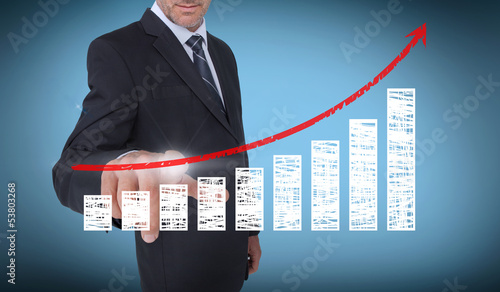 Businessman touching a chart with a red arrow pointing up