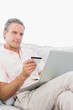 Man on his couch using laptop for shopping online