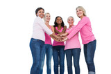 Cheerful women wearing breast cancer ribbons with hands together