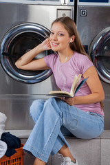 Woman With Book Listening To Music In Laundry