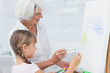 Grandmother and granddaughter painting together