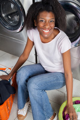 Happy Woman Sitting In Laundry