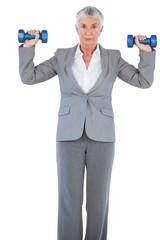 Businesswoman holding dumbbells