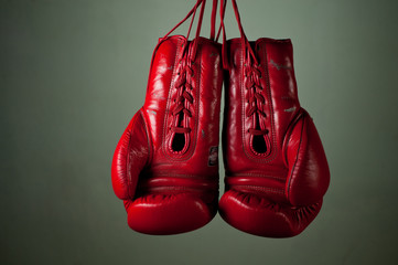 Boxing gloves hanging from laces on a grey background
