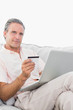 Man on his couch using laptop for shopping online smiling at cam