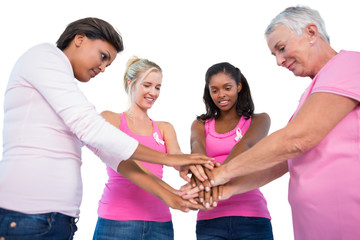 Smiling women wearing breast cancer ribbons putting hands togeth