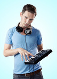 Deejay with headphones pressing keys on midi keyboard