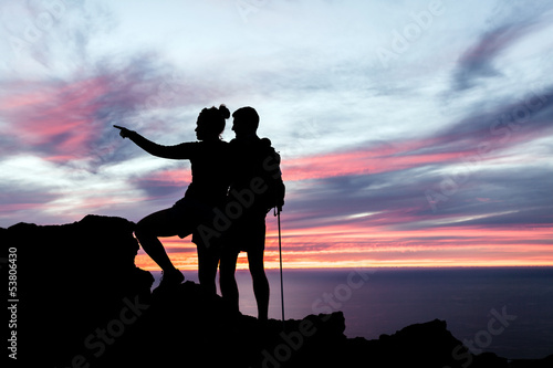 Couple hikers silhouette in mountains