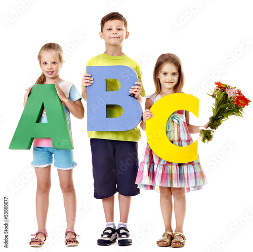 Children holding abc.