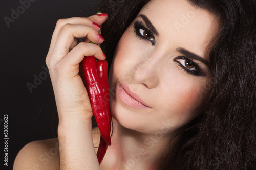 portrait of beautiful brunette girl with hot red cayenne