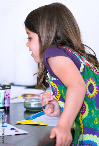 Expressive portrait of a pretty young girl doing paint with her