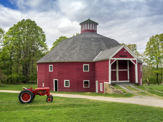 Red New England barn with vintage tractor