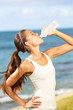 Fitness woman drinking water after beach running