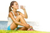 Fitness woman drinking water after workout outside