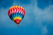 Leinwanddruck Bild - Brightly colored hot air balloon with a sky blue background