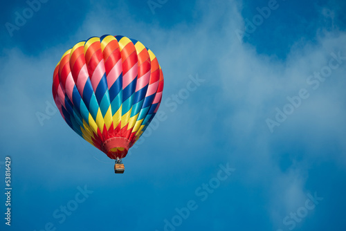 Leinwanddruck Bild Brightly colored hot air balloon with a sky blue background