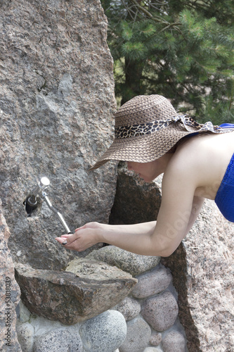 Woman held out her hands and drinks water from a spring