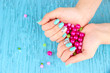 Beautiful woman hands with blue manicure holding pink beads,