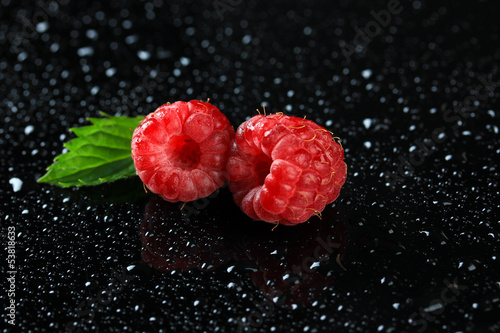 Ripe sweet raspberries with drops on dark background