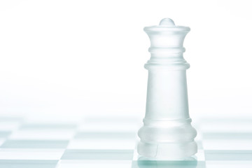 Glass chess queen is standing on board, cut out from white backg