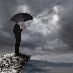Business Man with umbrella look rainstorm cloud